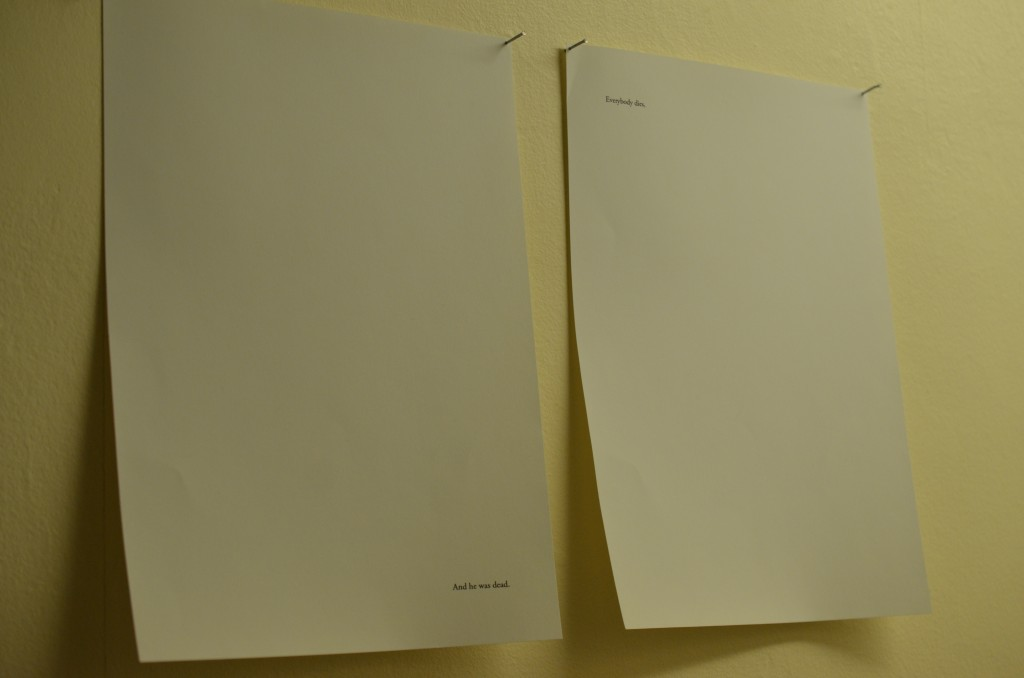 two sheets of a4 paper hang are pinned to a wall. Each sheet has a single line of typewritten text on it. In the bottom right hand corner of the left sheet, is written the line 'And he was dead.' full stop. In the top left hand corner of the right sheet, is written the line 'Everybody dies,' comma.