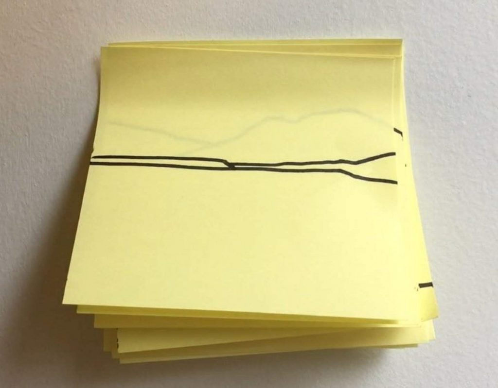 A post-it note, stuck on top of many other post-it notes, bearing a two-line drawing representing a horizon.