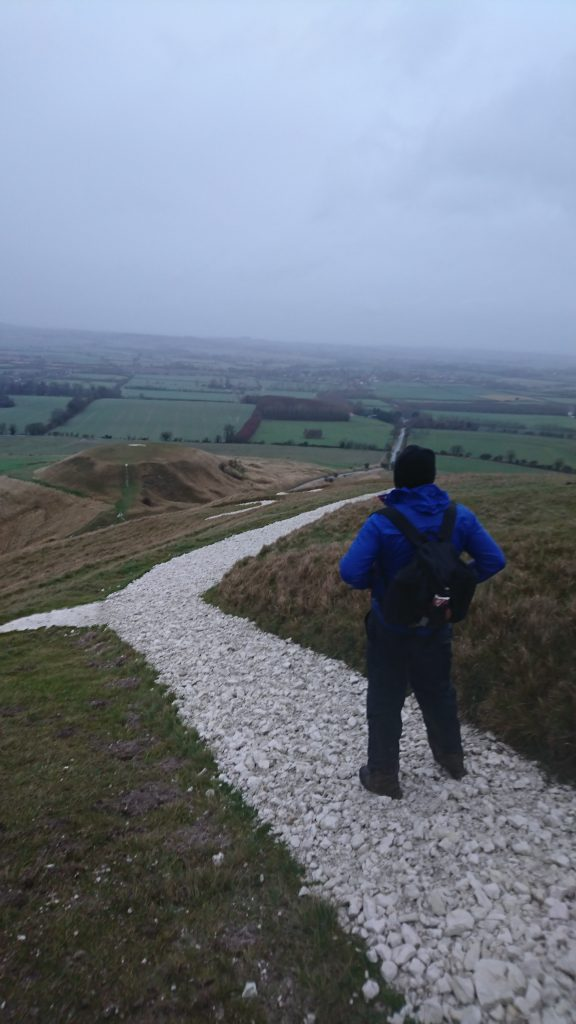 A man pictured from behind stands on a white chalk path, looking out over a misty landscape.